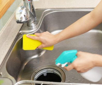 cleaning kitchen sink with sponge and cleaning detergent